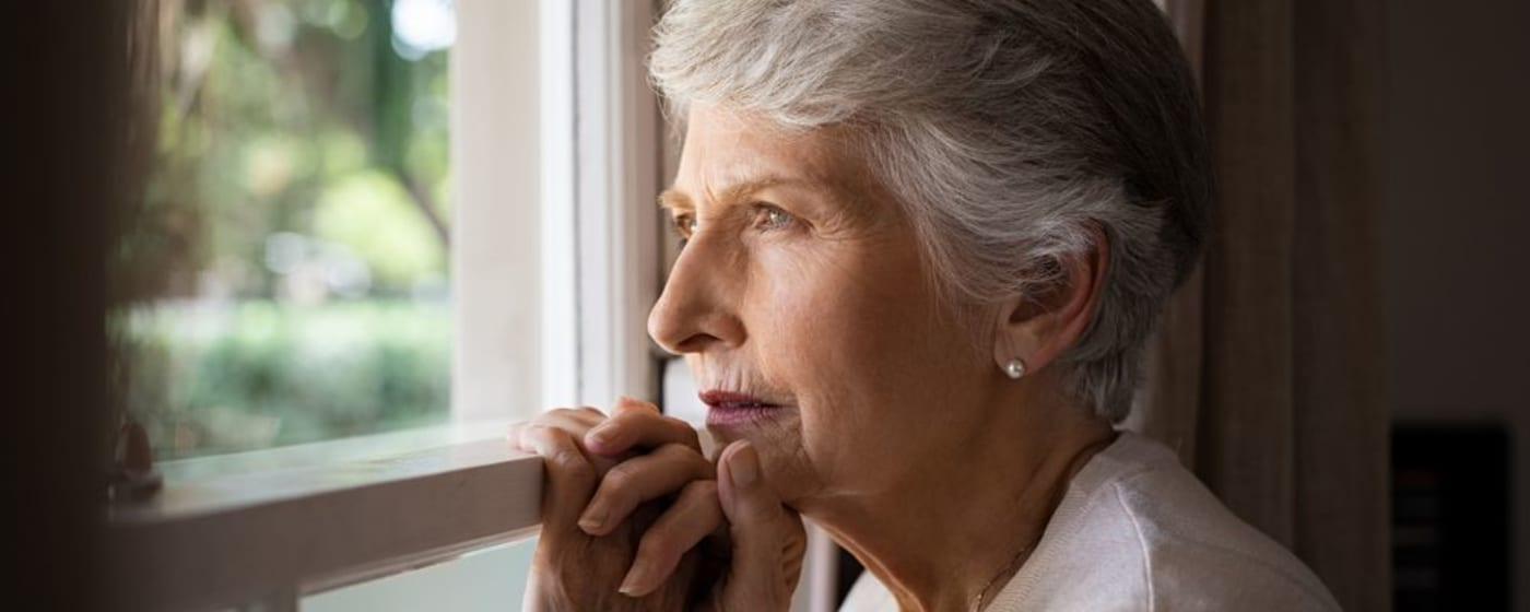 Lonely older women looking out the window
